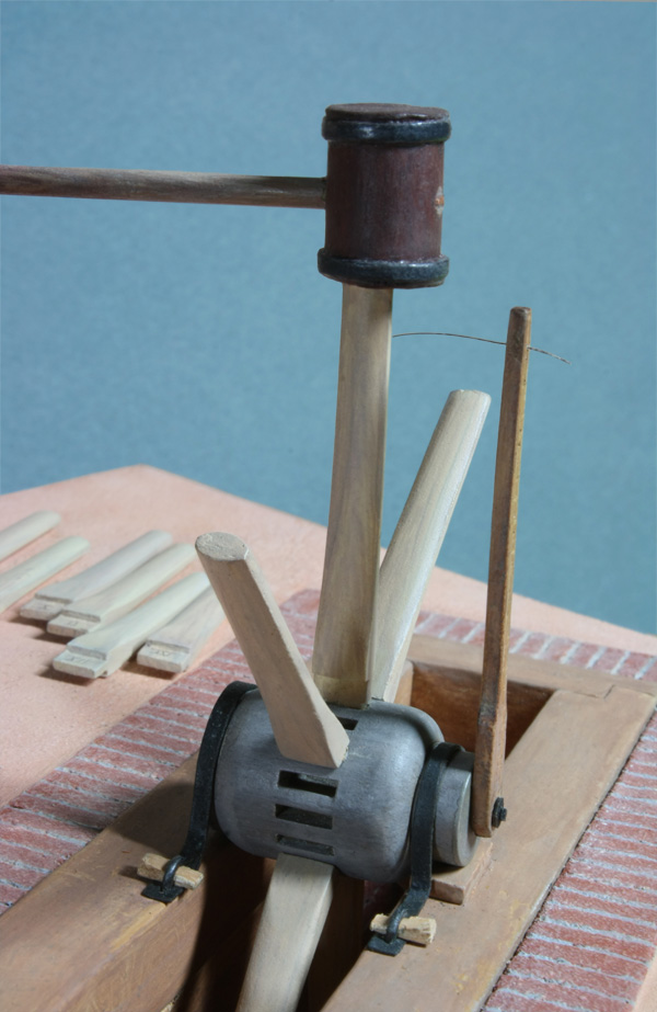 Close-up of 1/20th scale Conestoga wheel hub with spokes being driven in